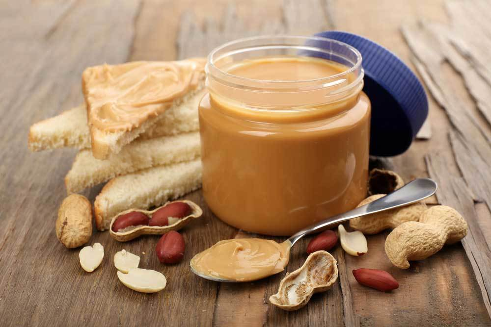 Open jar of peanut butter on wooden table with slices of bread, open peanut shells, and a spoon full of peanut butter.