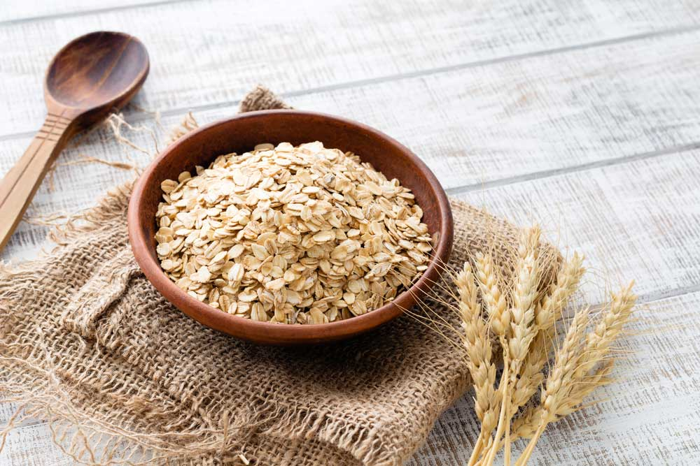 bowl of oats on a piece of burlap with a wooden spoon and wheat stalks