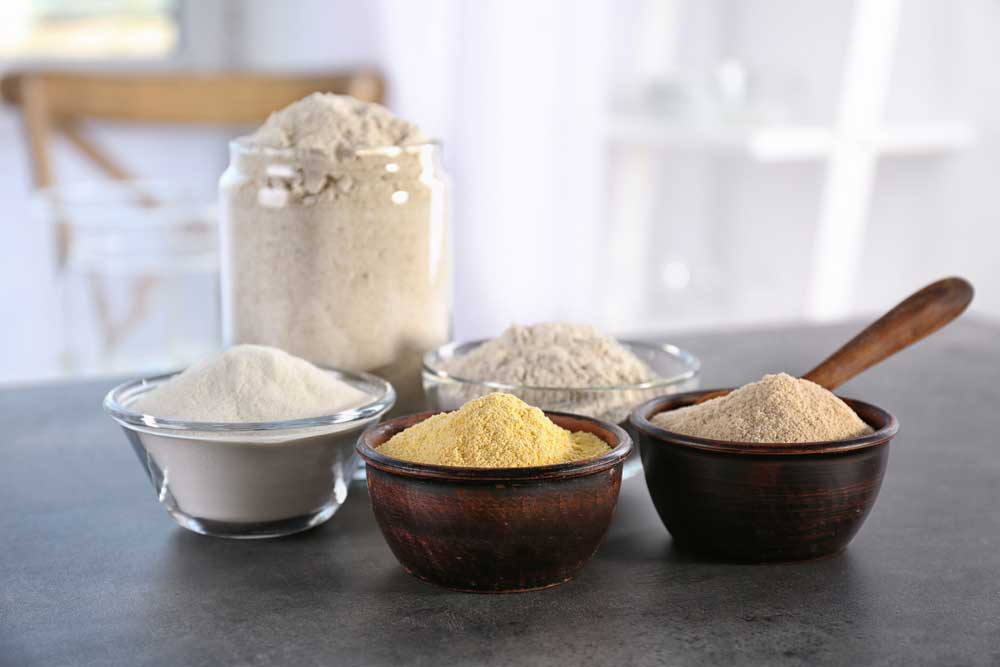 variety of flour types in different containers on a kitchen counter
