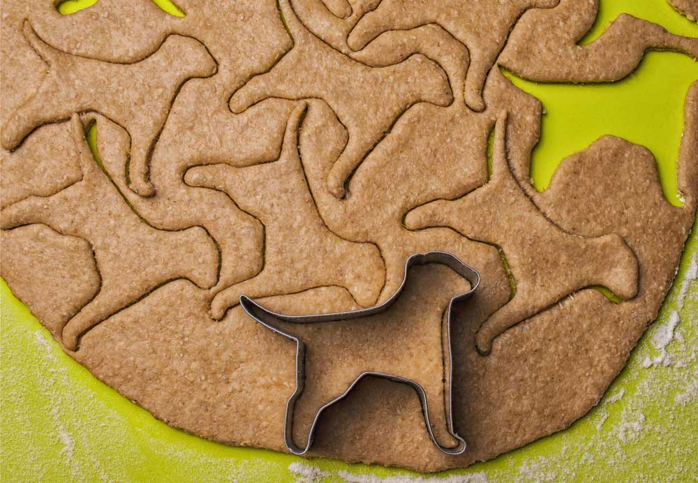 dough rolled out on green surface with dog shapes cut out of the dough and a dog cookie cutter.