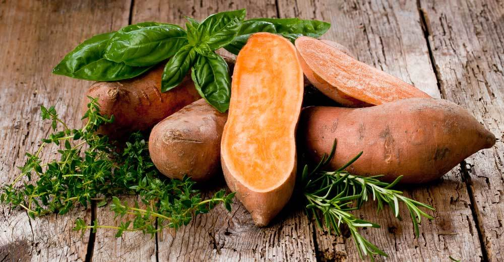 pile of sweet potatoes on wooden table surrounded by herbs.