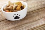 a white dog food bowl with a black paw print full of dog bone shaped treats on a wooden table.