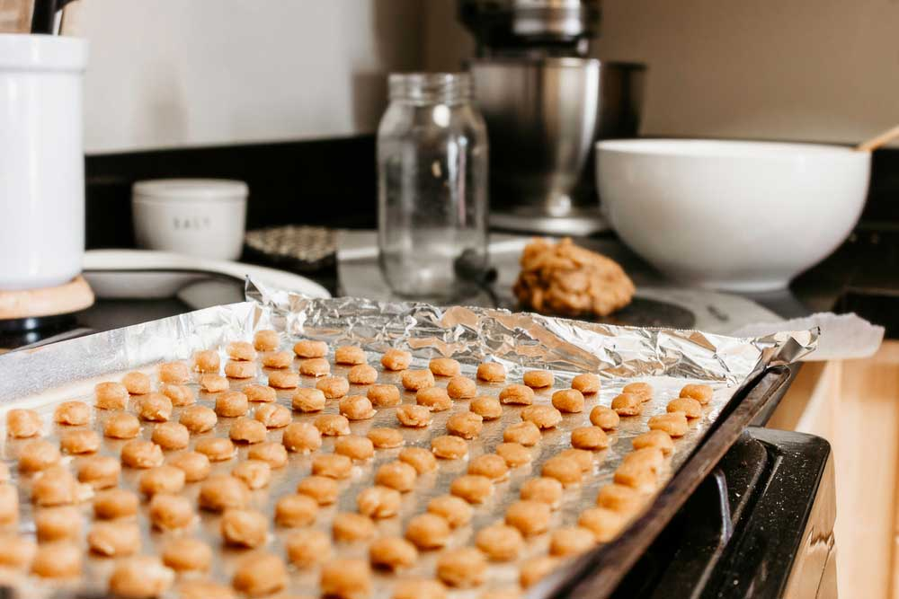 dog treats on a foil lined baking sheet sitting on a stove top next to a ball of dough and a mixing bowl.