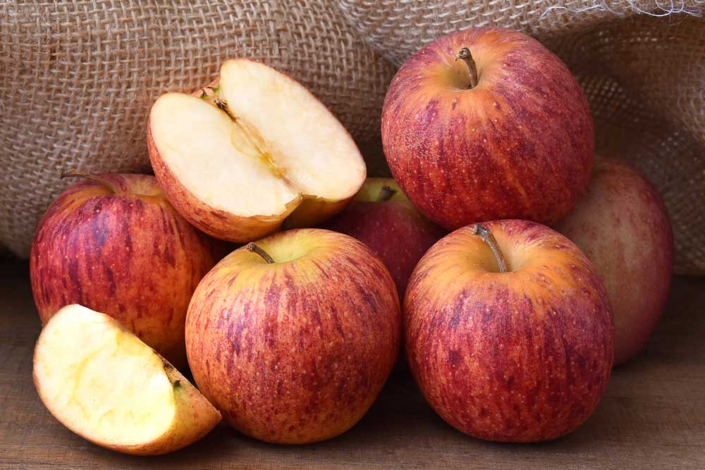 Red apples on a wooden surface in front of a burlap sack with one apple cut open