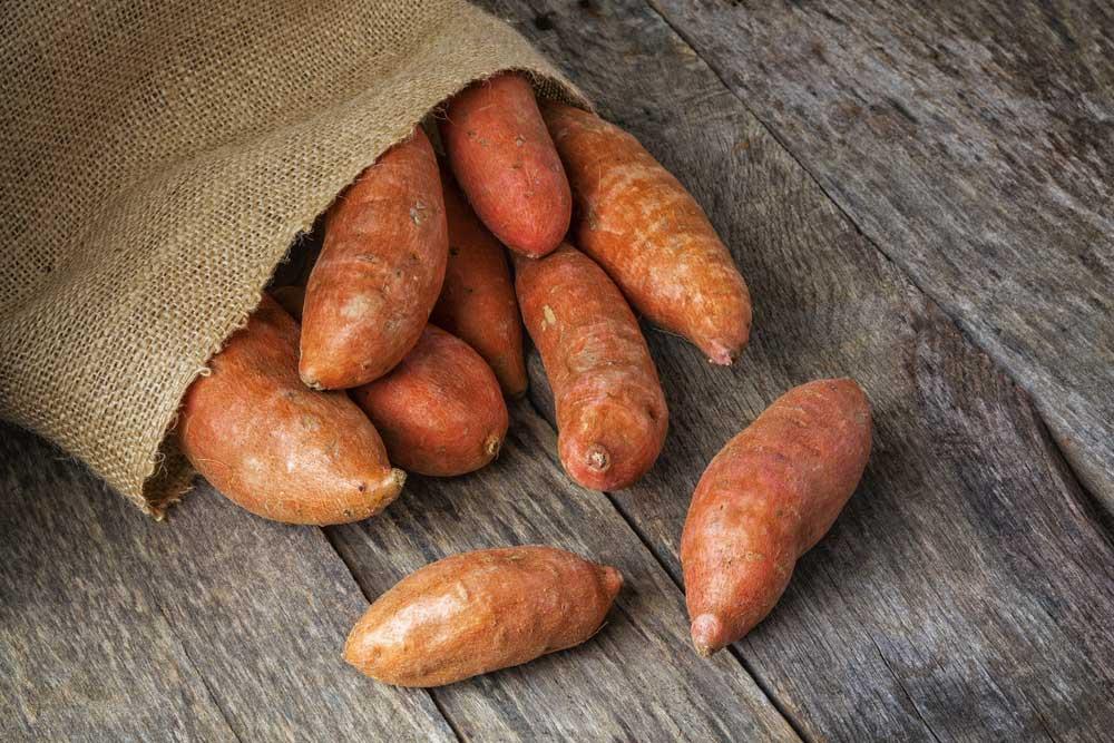 burlap sack of sweet potatoes spilling onto wooden surface