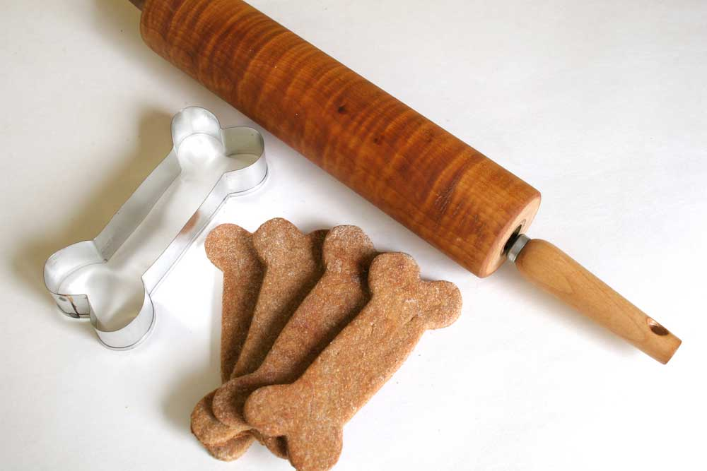 Rolling pin, dog bone shaped cookie cutter and dog bone shaped dog treats on a white background.