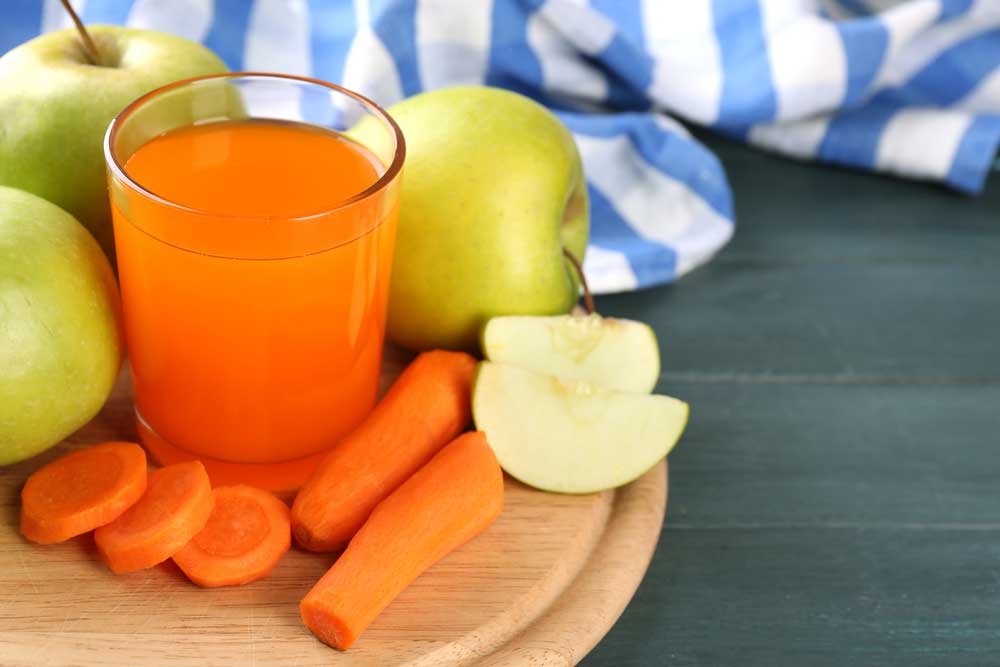Apples and carrots on a cutting board with a glass of juice.