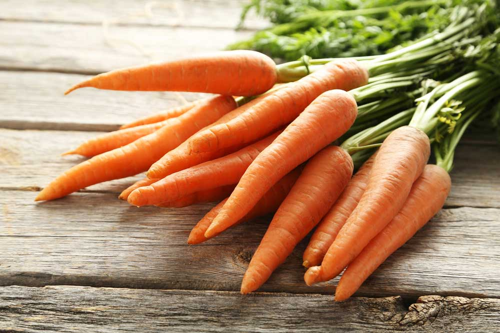 bunch of carrots with tops still on on a wooden table.