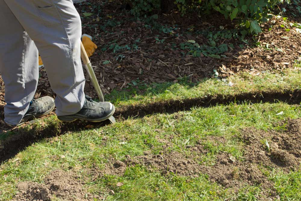 Man digging a border in grass