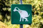 Green sign on post showing dog potty area