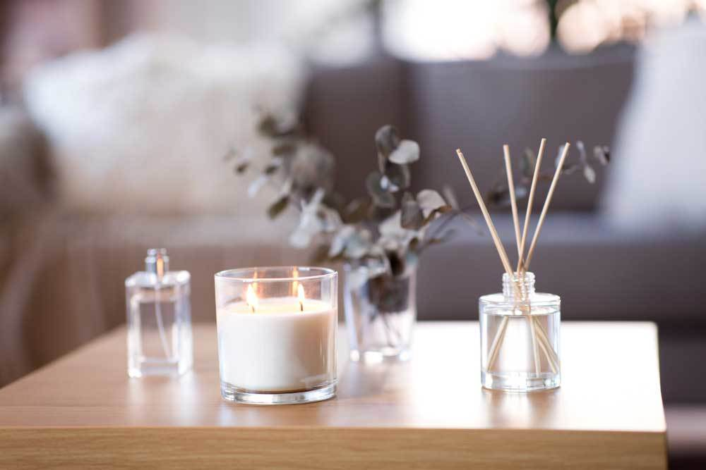 Scented candles, diffusers, and perfume spray on a coffee table.
