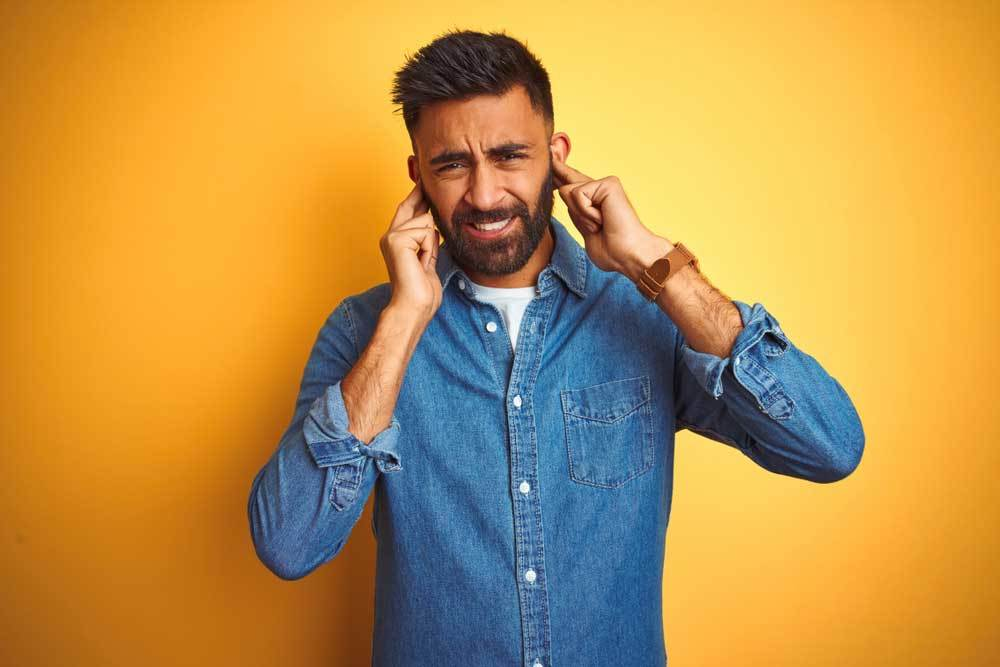man on yellow background pluggin his ears