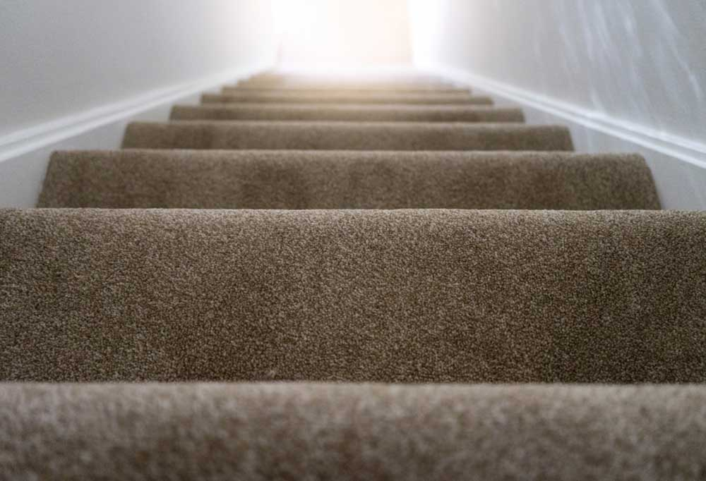 Closeup of stairs covered in tan carpet