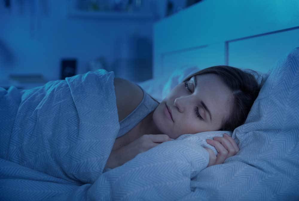 woman sleeping in bed with blue tint