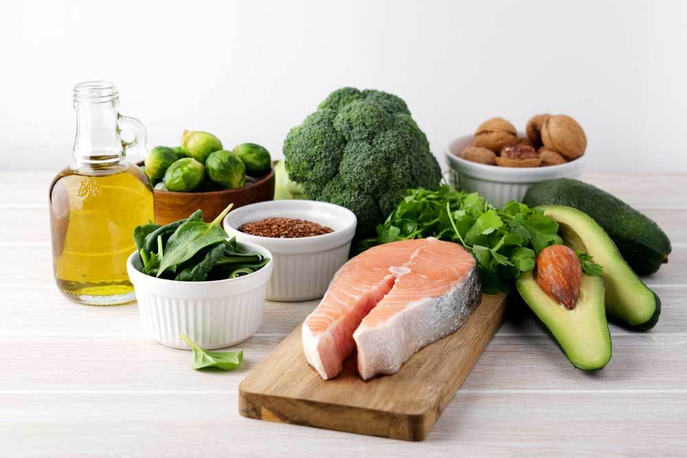 Veggies, meats, oils and nutes on a wooden table
