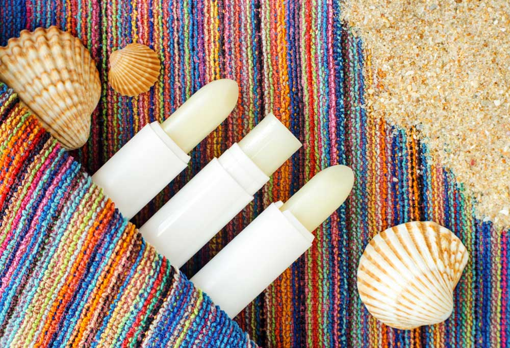 Balm in a twist up stick on a blanket at the beach with shells and sand