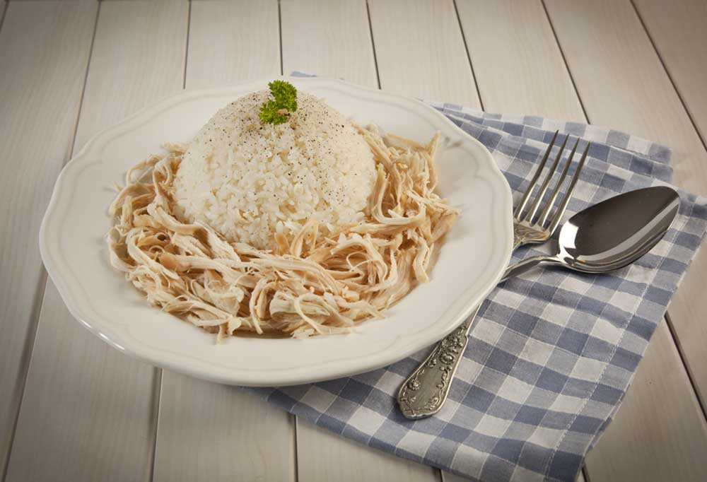 Chicken and rice on a white plate with a blue check napkin with spoon and fork.