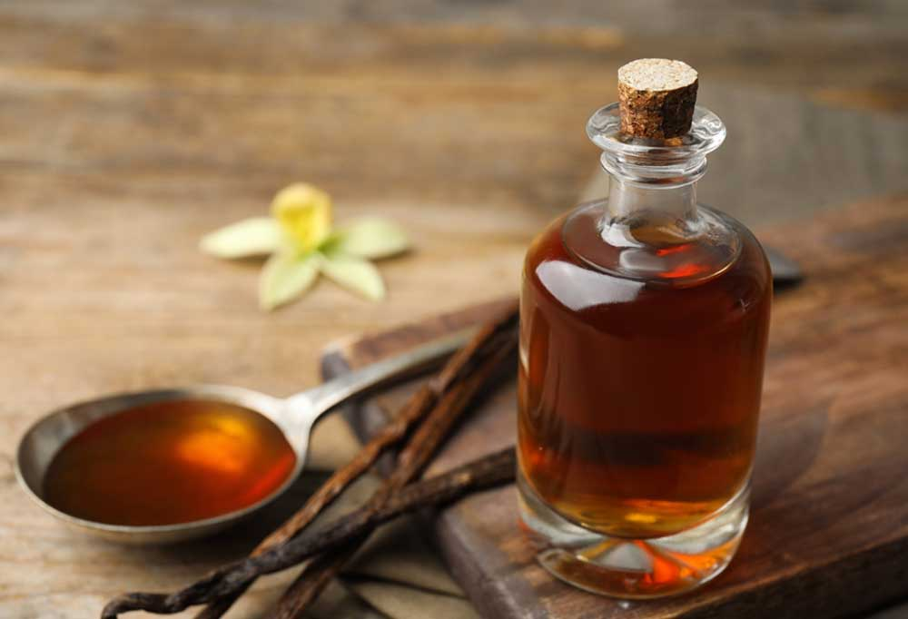Vanilla extract in a bottle with a tablespoon filled with extract and vanilla beans on a wood table