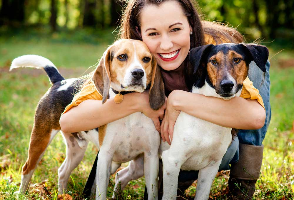 Woman hugging 2 dogs outdoors