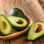 avocados sliced in half on wooden table