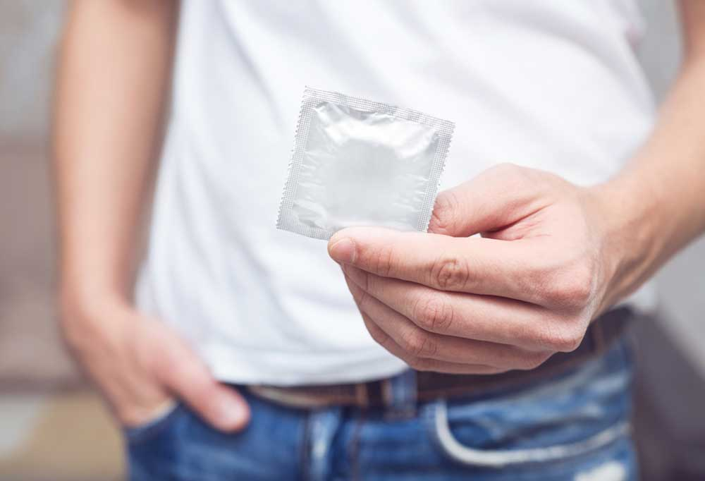 Man holding out silver foil wrapped condom