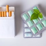 A pack of cigarettes and pack of nicotine gum isolated on white background