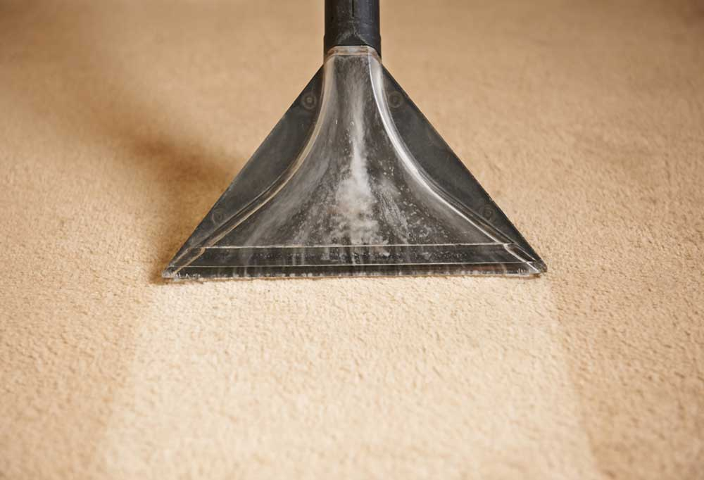 Carpet shampooer being pulled across tan capet