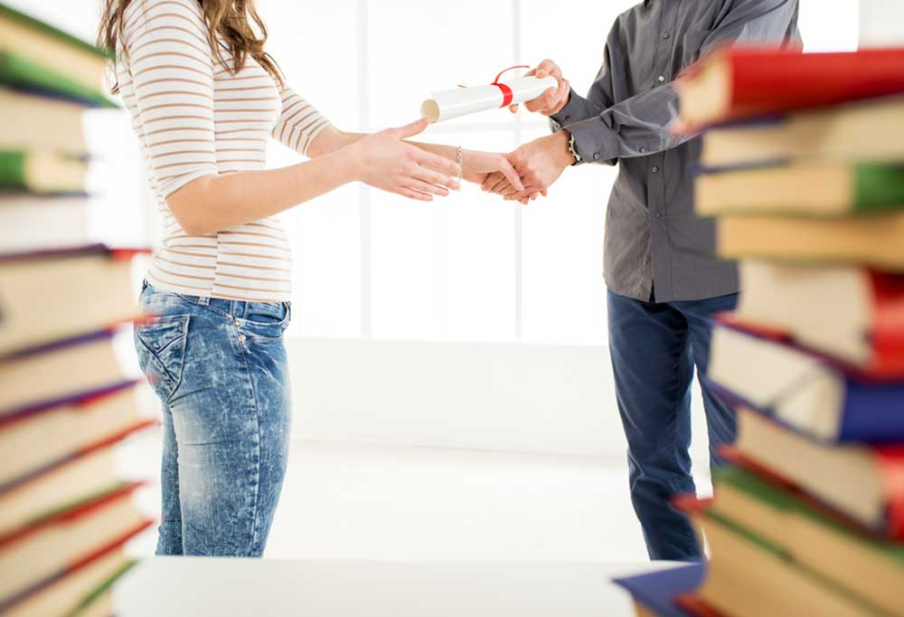 Person handing another person a diploma, blurred books in the foreground