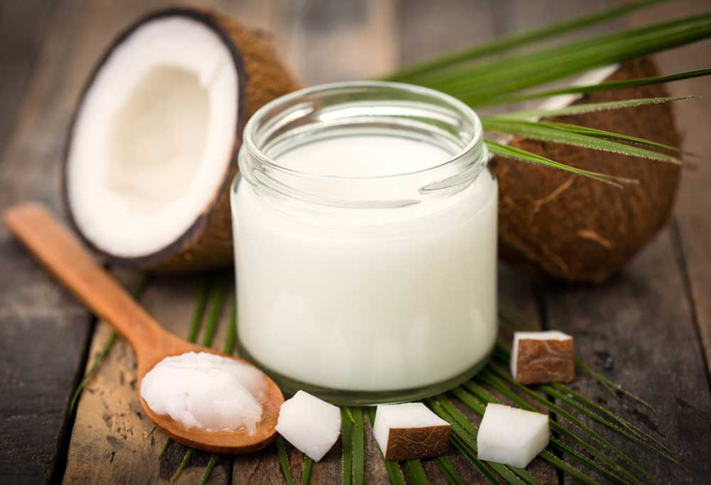 Coconut oil in jar surrounded by coconut halves and pieces and coconut oil on a spoon