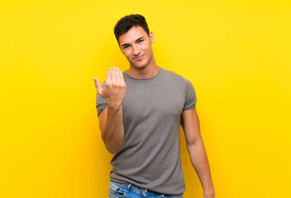 man on yellow background using hand signal for come to me
