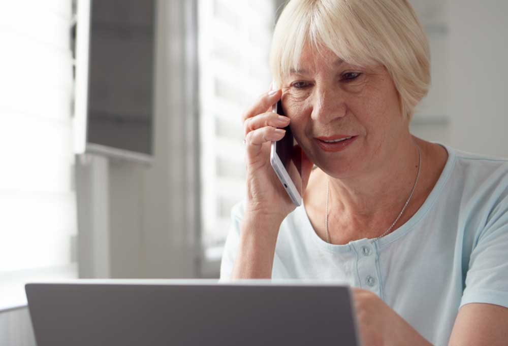 Woman on telephone while looking at laptop