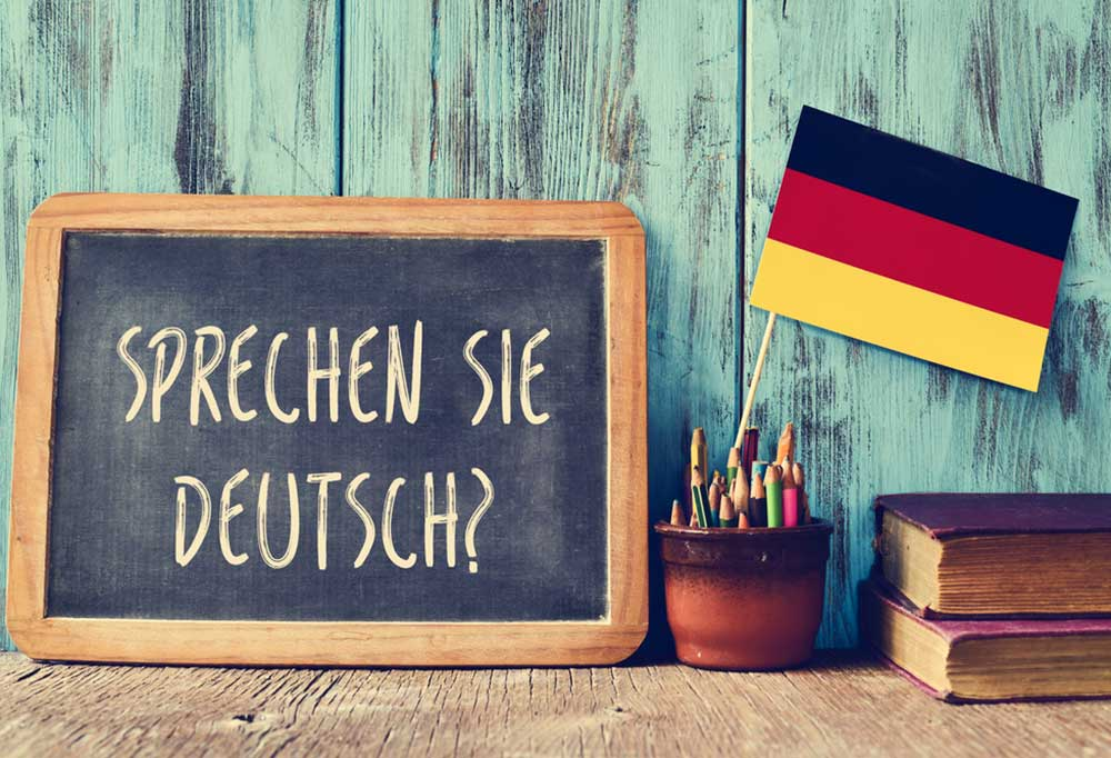 """a sign that reads """"Sprechen Sie Deutsch?"""" on a desk with a black, red, and yellow flag in a pencil holder with 2 books."""