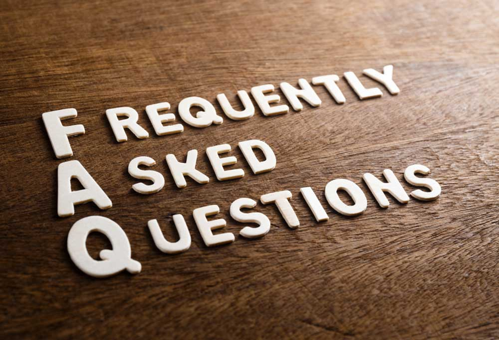 the words Frequently Asked Questions spelled out on a wooden table
