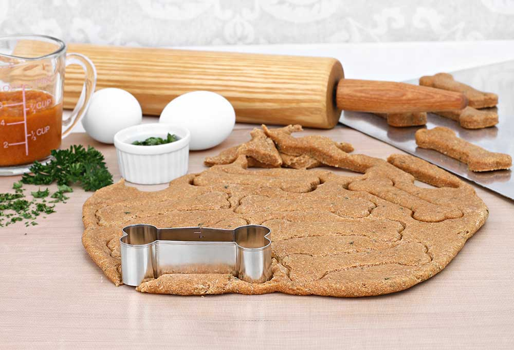 Cookie dough rolled out on counter surrounded by ingredients and baking tools, including a bone shaped cookie cutter.