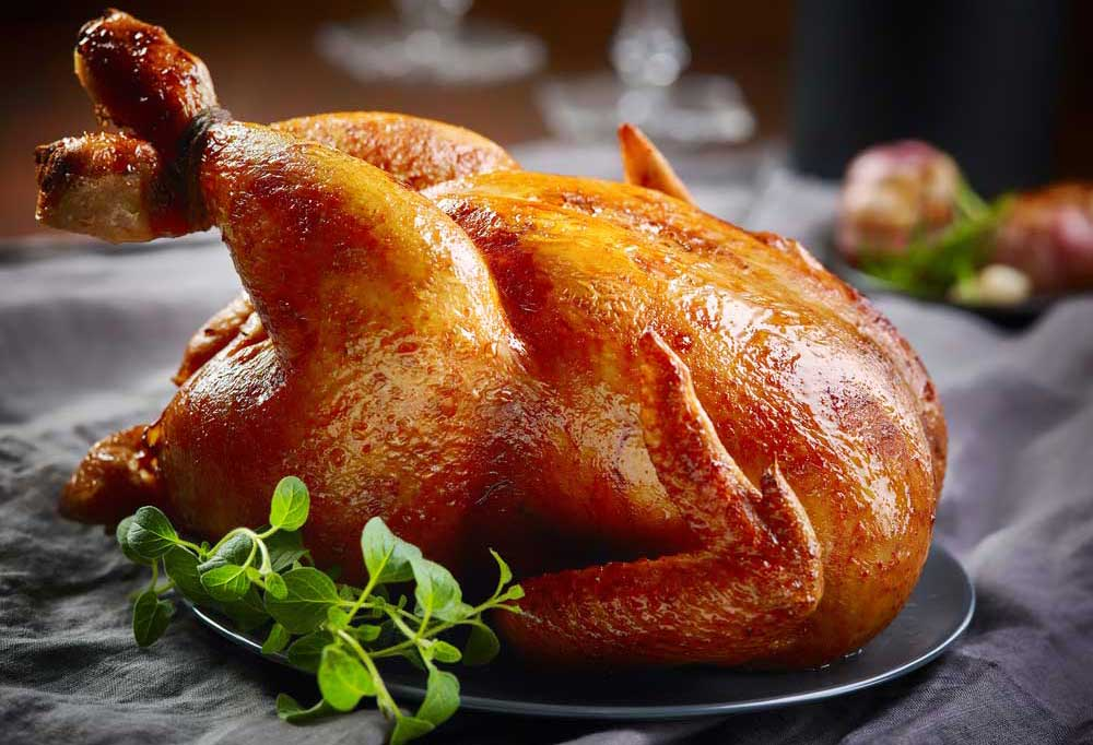 Roasted chicken on platter resting on tablecloth covered table