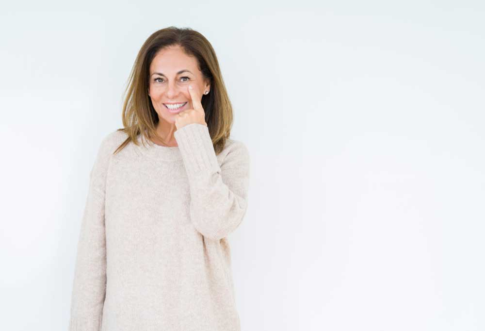 woman on a white background pointing to her eye