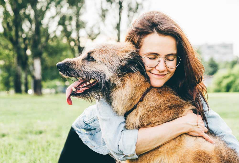 Woman with glasses outdoors hugging a shaggy dog