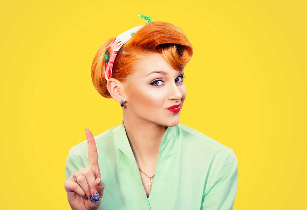 Woman with a 40-50 era look on a yellow background with one finger held up as if saying no