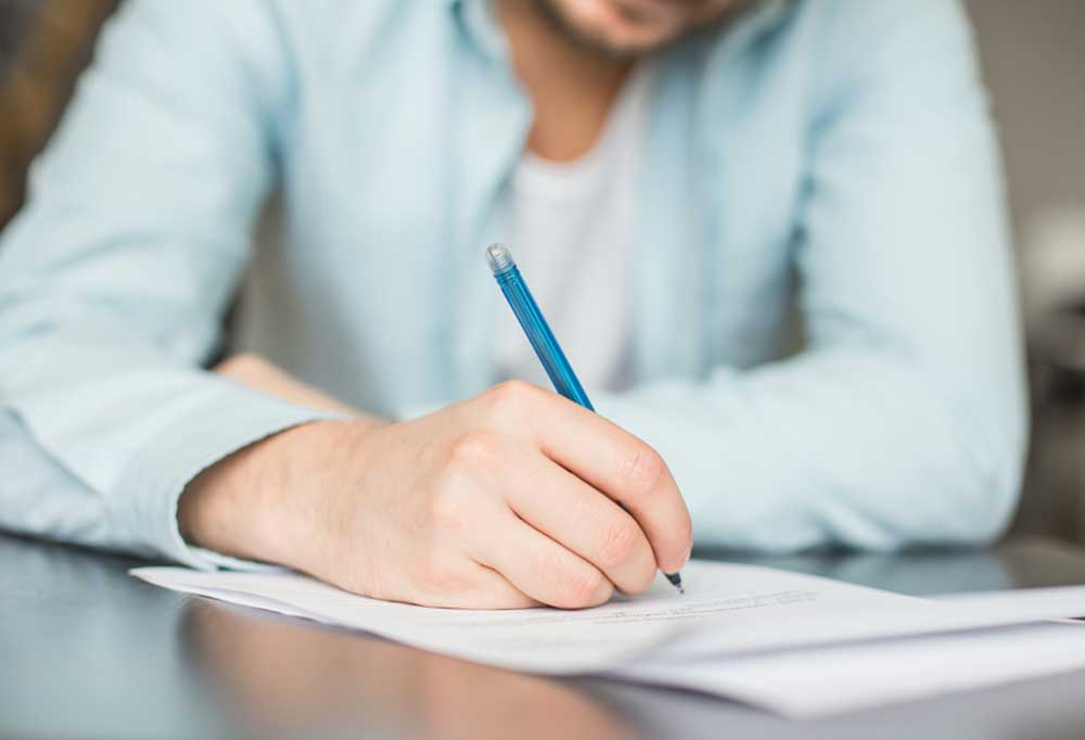 person writing a letter with an ink pen and paper