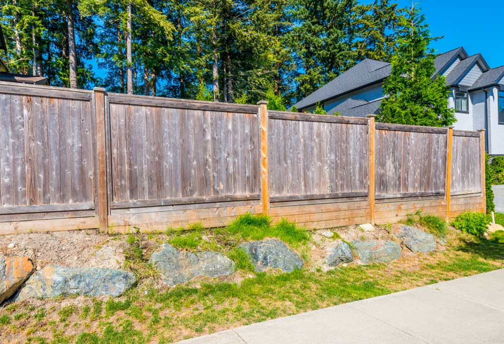 Privacy fence around yard with large rocks surrounding the bottom