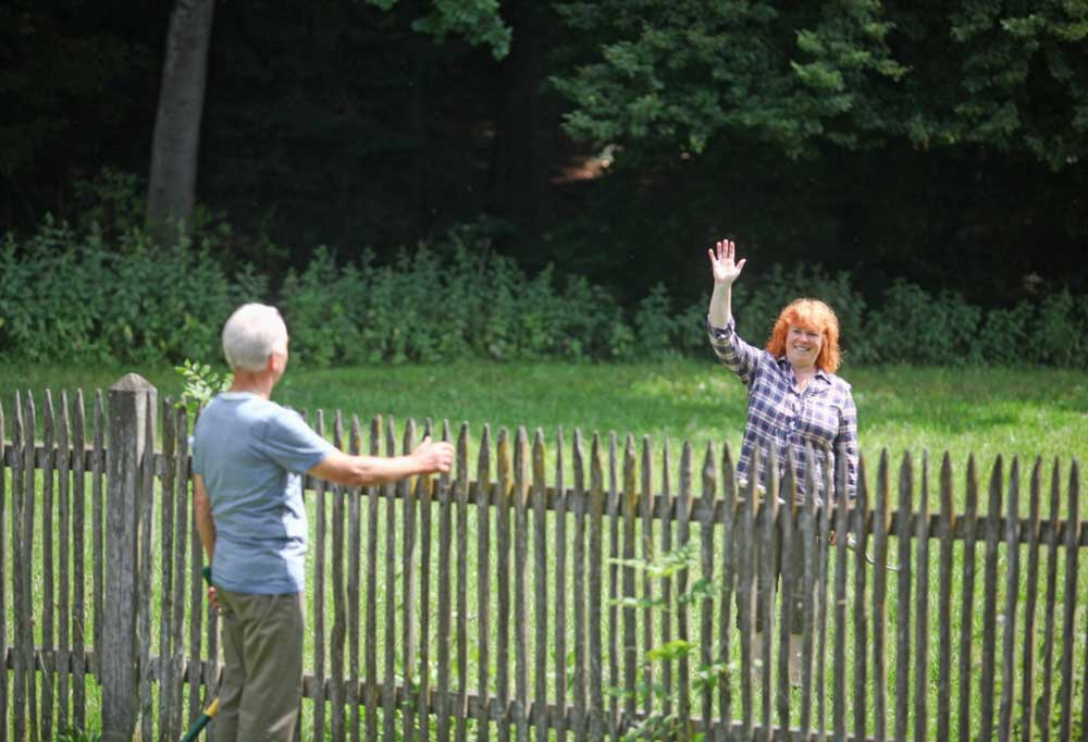 Neighbors talking over a picket fence