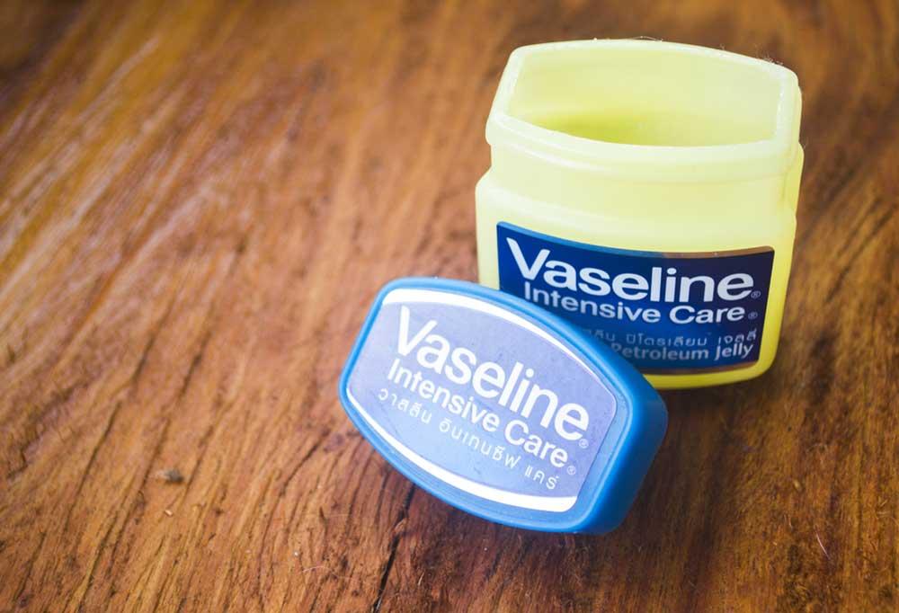 Jar of Vaseline sitting open on a wooden table