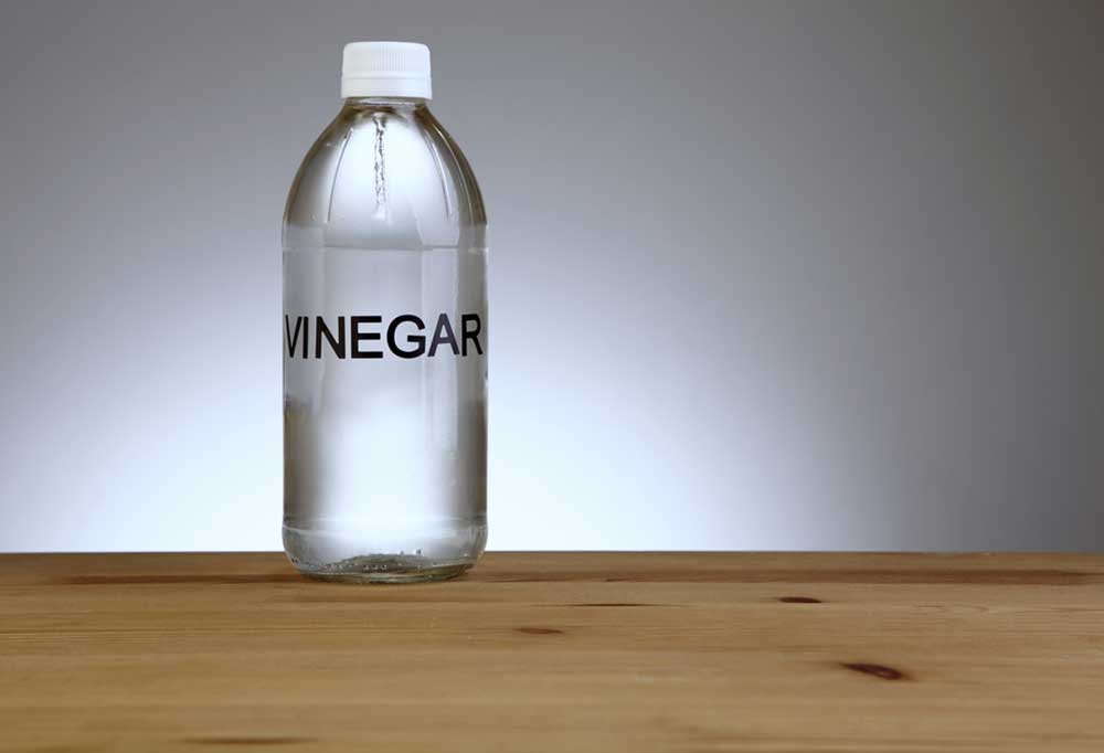 Bottle of white vinegar on a table with a grey background