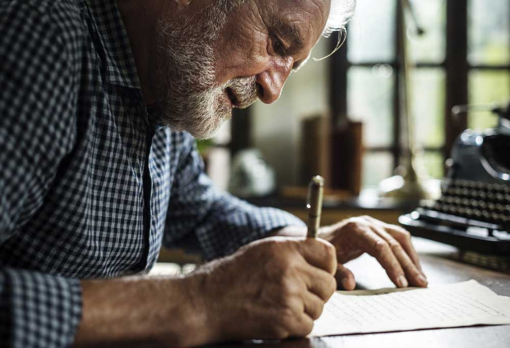 Older man writing a letter with pen and paper
