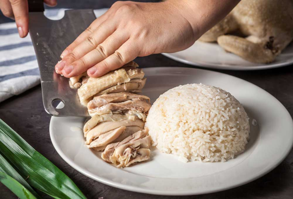 Hand sliding cooked chicken off of a knife onto a plate with rice