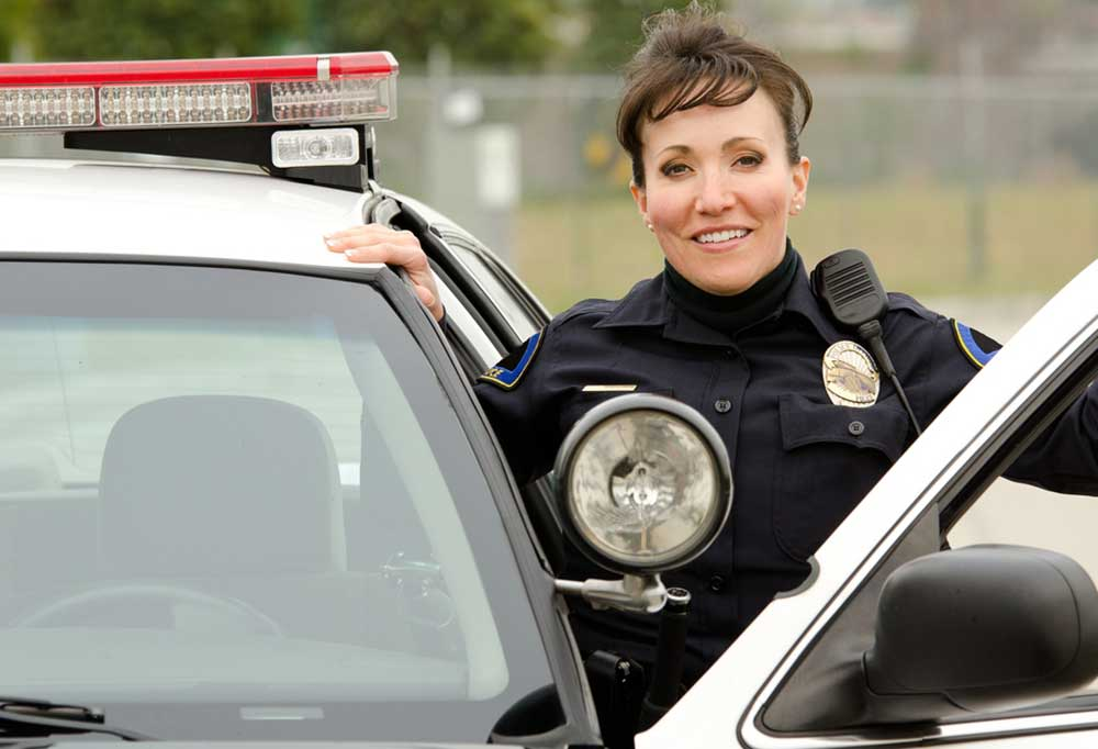 A police officer smiling in uniform while standing in her open police cruiser car door