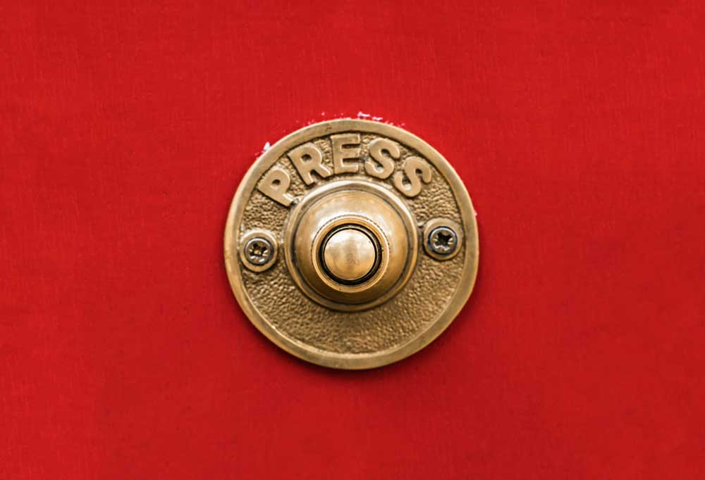 """Round doorbell that says """"Press"""" on a red backgroun"""