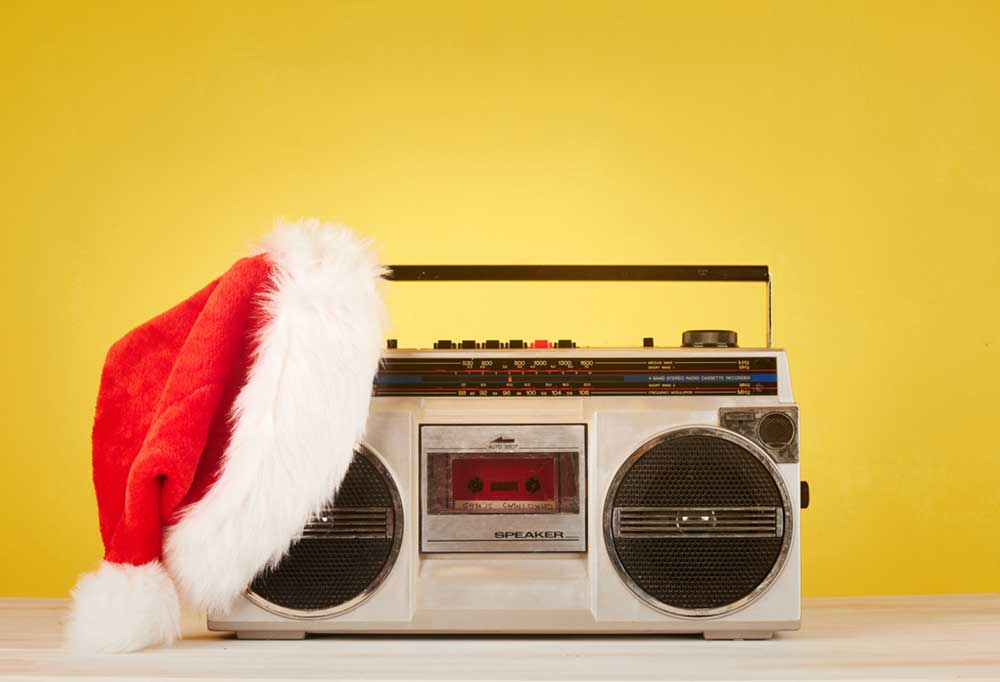 Portable stereo (boom box)  on a yellow background with a Santa hat draped over one end
