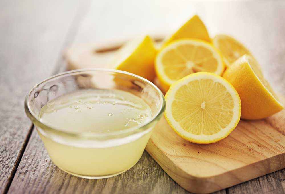 Lemon juice in a bowl sitting on a wooden table sitting next to a cutting board containing lemon halves