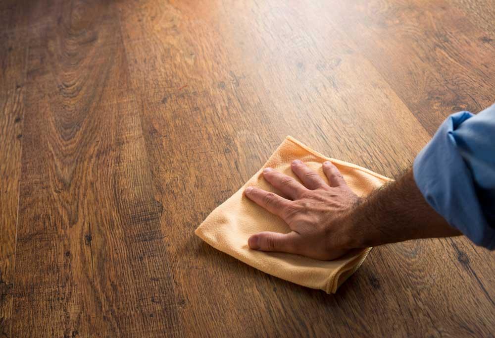 Man's hand with yellow rag wiping hard wood floor